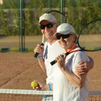 Happy cute senior couple playing tennis outdoors